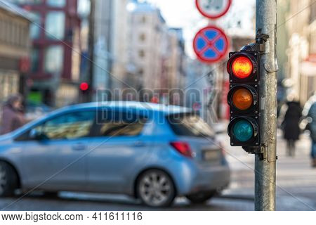 Close-up Of Small Traffic Semaphore With Red Light Against The Backdrop Of The City Traffic