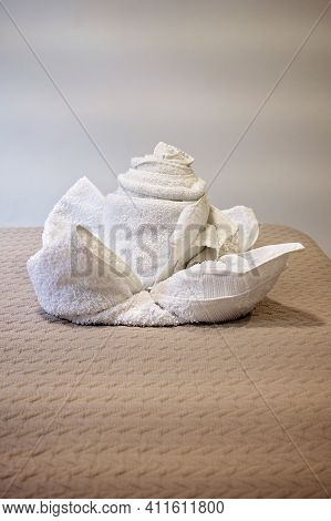 Two Bath Towels Folded Into A Decorative Flower Shape - Towel Art On A Bed