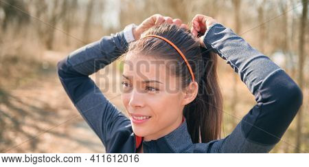 Asian runner getting ready to run outside tying her hair into ponytail for hiit workout jogging training. Happy smiling athlete jogger banner.