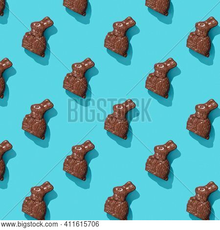 Chocolate Easter Bunny on blue background pattern, flat lay, top view
