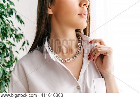 Silver Bijouterie Chain On Woman Neck. White Background With Green Plant.
