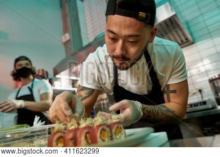 Portrait Of Professional Sushi Chef Carefully Adding Final Touch With Dedication To His Perfect Set