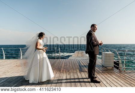 Groom With The Bride At The Sea. Meeting Of The Bride And Groom On The Pier Near The Sea. Wedding Co