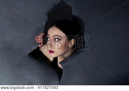 A Young Girl In Theatrical Makeup, Peering Through A Hole In The Gray Paper.