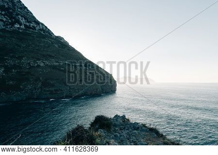 Scenic View Of Rocky Promontory In The Coast With Hazy Weather At Sunset