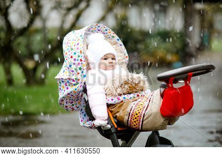 Cute Little Beautiful Baby Girl Sitting In The Pram Or Stroller On Cold Day With Sleet, Rain And Sno