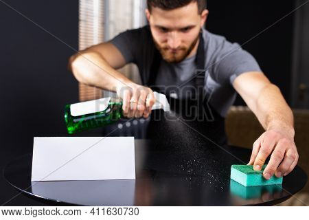 Housekeeping And Cleaning Service Concept. Smiling Young Man Using Spray Detergent, Standing In Offi