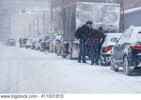 Tula, Russia - February 13, 2020: Two Men Standin Near Car Parked On Side Of City Road During Heavy