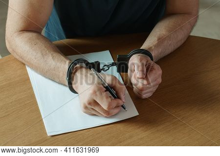 Men Hands With Handcuffs Fill The Police Record, Confession. On Top Of The Police Investigative Dete