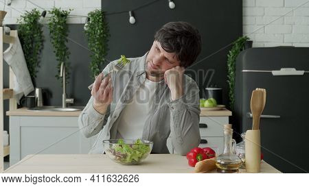 Unhappy Man Eating Vegetable Salad At Table In Kitchen. Displeased Young Man Eating Green Leaf Lettu