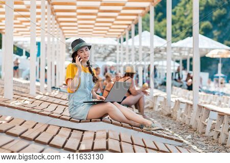 A Young Pretty Woman Is Sitting On A Sunbed On The Beach With A Laptop And Making A Phone Call. The