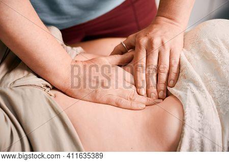 Close Up Of Physician Hands Massaging Woman Abdomen During Medical Examination. Doctor Examining Pat