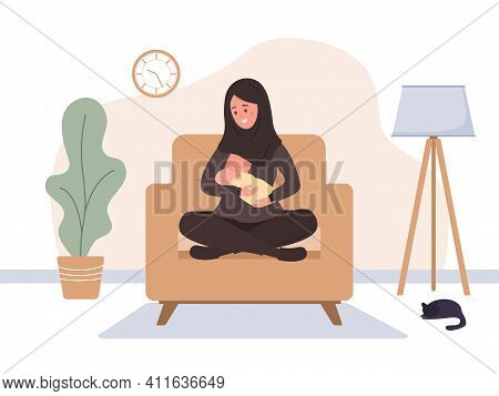 Breastfeeding Concept. Young Islamic Mother Sitting On Armchair And Nursing Newborn Baby. Natural Fe