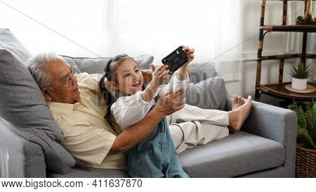 Happy Family Uncle Senior Male Selfie Taking Photo With Daughter With Mobile Smartphone On Sofa In T