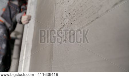 Aligning The Wall With Wire. Leveling The Mortar. A Mortar Worker Uses A Screed To Level The Wall. A