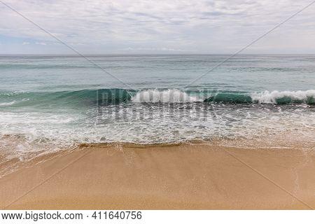 Seascape Background. Sandy Beach, Milky Foam Waves, Blue Ocean. Scenic Waterscape. Horizon Line. Nat