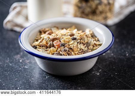 Beakfast cereals in bowl. Healthy muesli with oat flakes, nuts and raisins on black table.