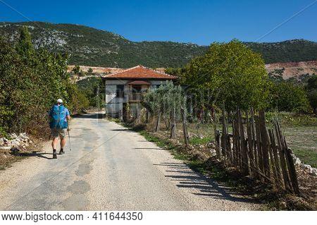 Hiking Lycian way. Man is trekking through Bezirgan village on Lycian Way trail along old broken ragged fence, Outdoor activity in Turkey