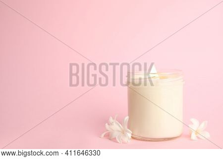 Beautiful Candle With Wooden Wick And Flowers On Pink Background, Space For Text
