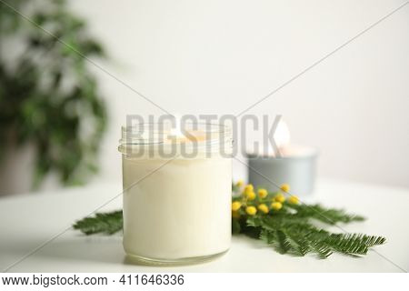 Beautiful Candle With Wooden Wick And Flowers On White Table