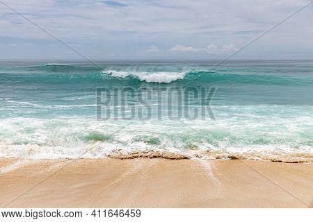 Seascape Background. Sandy Beach, Milky Foam Waves, Blue Ocean. Scenic Waterscape. Horizon Line. Clo