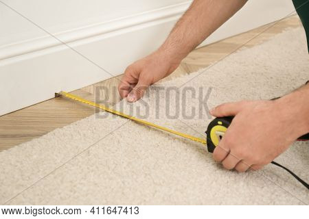 Worker With Measuring Tape Installing New Carpet Indoors, Closeup