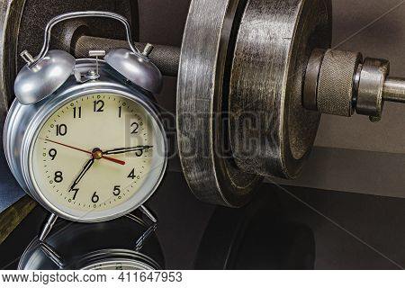 Time For Morning Workout. Alarm Clock On The Background Of Dumbbells. Conception Of Sports And Healt