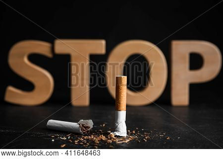 Broken Cigarette Near Word Stop On Black Table. Quitting Smoking Concept