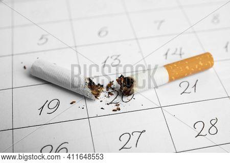 Cigarette Stubs On Calendar Sheet, Closeup. Quitting Smoking Concept
