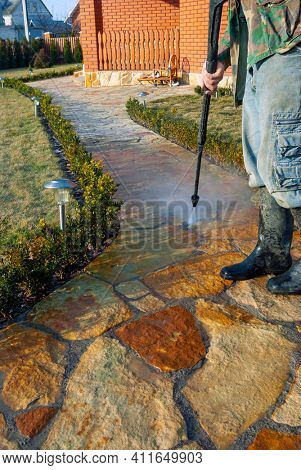 Outdoor cleaning street with high pressure power washer, washing stone garden paths.