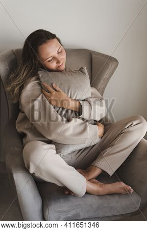 Young Woman Dressed In Grey Comfy Suit Sitting In A Cozy Armchair And Holding A Small Decorative Pil