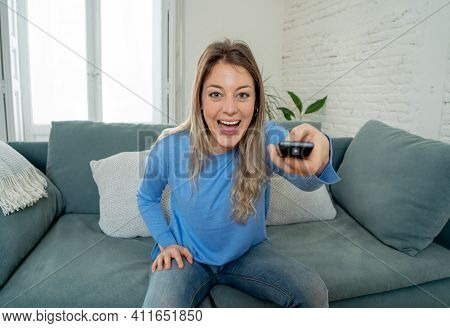 Lifestyle Portrait Of Cheerful Young Woman Sitting On The Couch Watching Tv Holding Remote Control