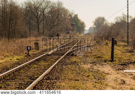 A Single, Straight Railway Track Stretching To The Horizon. It Is Early Spring, The Nearby Trees And