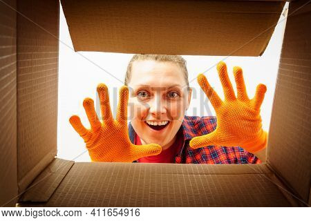 Young Woman Looks Inside The Box. A Woman Looks Into An Empty Box From The Inside And Shows Her Hand