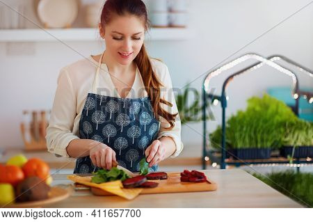 Woman Cutting Beetroot And Spinach Leaves For Organic Raw Salad At The Kitchen