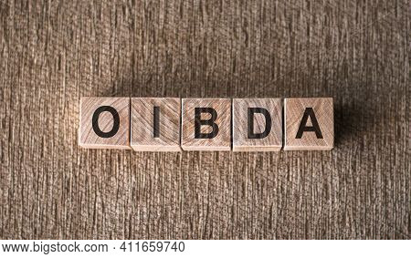 Oibda - Operating Income Before Depreciation And Amortization - Word Written On Wooden Blocks On A B