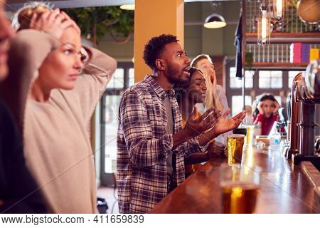 Group Of Disappointed Customers In Sports Bar Watching Sporting Event On Television