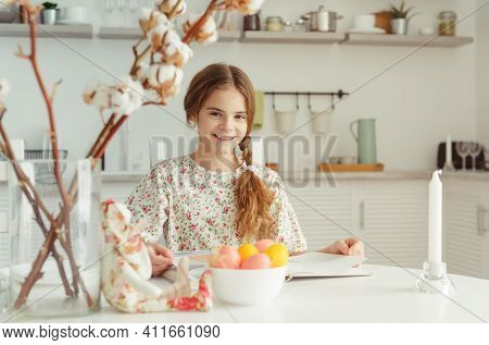 European Girl 10 Years Old In The Kitchen At The Table With Yellow, Pink Easter Eggs