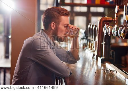 Unhappy Man Sitting At Pub Bar Drinking Alone With Glass Of Whisky