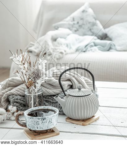 A Teapot And A Beautiful Ceramic Cup With Decor Details In A Hygge Style Living Room. The Concept Of