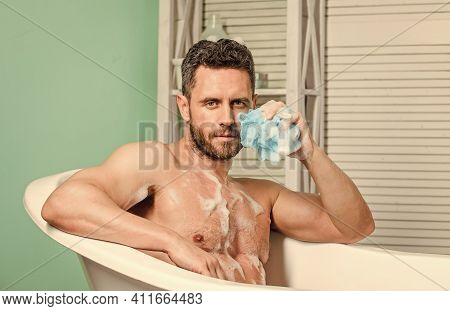 Pampering And Beauty Routine. Man Handsome Muscular Guy Relaxing In Bathtub. Macho With Sponge Take