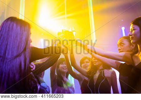 Young People Celebrating A Party, Drink And Dance . Group Of Friend Toasting Drinks While Having Fun