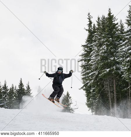 Male Skier In Ski Suit And Helmet Skiing On Fresh Powder Snow With Coniferous Trees And Sky On Backg