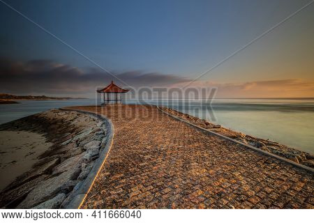 Sunrise On The Beach. Landscape Backgroud. Walking Path To Traditional Balinese Gazebo. Cloudy Sky.