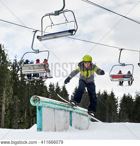 Snowboarder In Helmet Riding Snowboard Under Ski Lifts. Man Performing Tricks With Snowboard. Concep