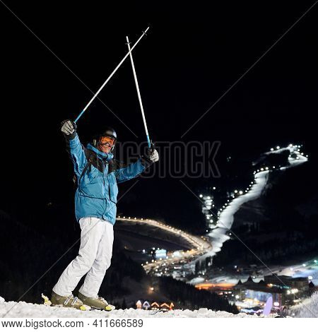 Male Skier In Winter Ski Jacket And Helmet Raising Ski Poles And Looking At Camera. Young Man In Ski