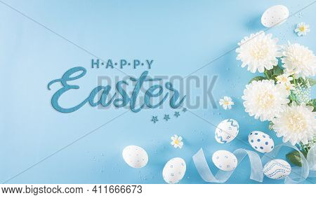 Happy Easter! Colourful Of Easter Eggs In With Flower On Pastel Blue Background. Greetings And Prese