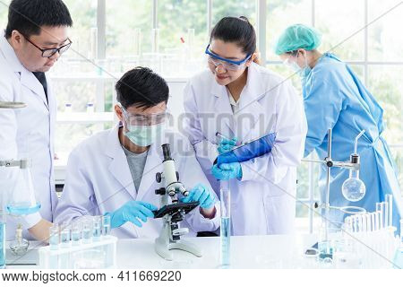 Team Work Asian Woman And Man Scientists Analyzing Study Data And Evaluating Microscope Success For