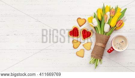 Colorful tulip flowers bouquet, heart shaped cookies and coffee. Top view flat lay with space for your greetings