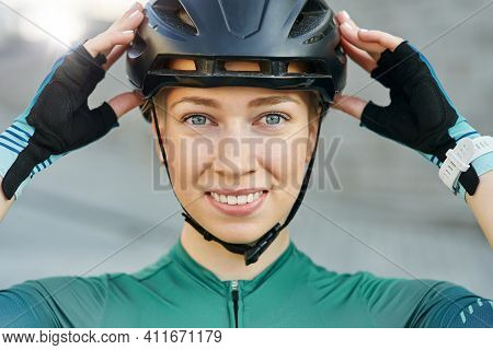 Portrait Of Cheerful Young Woman, Female Cyclist Putting On Biking Helmet, Smiling At Camera While P
